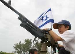 En israelsk gutt på Gazastripen leker med et maskingevær i protest mot den planlagte tilbaketrekkingen (Scanpix/Reuters)
