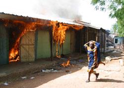 Ei jente løper forbi et hus satt i brann av den kristne militsen i Yelwa. (Foto: G.Osodi, AP)