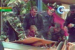 Politimenn løfter ut den tsjetsjenske presidenten Akhmad Kadyrov. Foto fra den russiske tv-stasjonen NTV. AP/Scanpix.