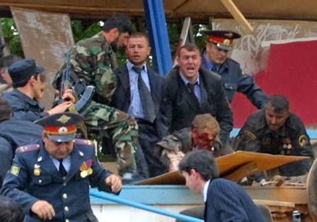 En hardt skadd tsjetjensk president Akhmad Kadyro løftes av politi. Han døde senere på sykehuset. (Foto: Musa Saulayev, AP/Scanpix)