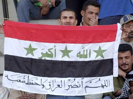 En irakisk supporter holder opp ett flagg der det står