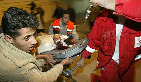OVERLEVDE: Flere palestinere ble drept av raketter tirsdag morgen. Her fraktes en av de sårede til sykehuset. (Foto: AP/Kevin Frayer)