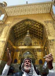 Gammel mann med hellig bok ber foran Imam Ali-moskeen (Scanpix/Reuters)