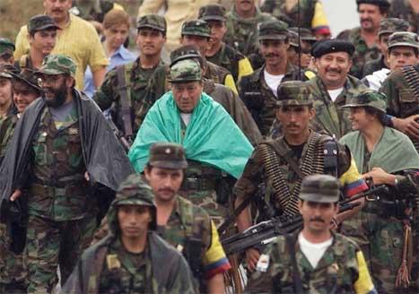 FARC-sjefen Manuel Marulanda i grøn poncho saman med ein del av geriljasoldatane sine. (Foto: AFP/Scanpix)