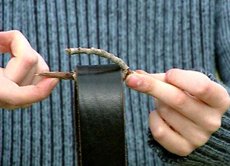 Sett skinnbeltet inni hakket på kvisten og plasser enden av kvisten på fingeren. (Foto: NRK)