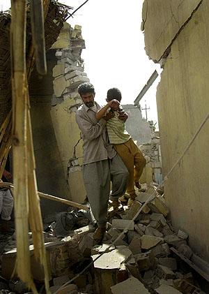 En iraker bærer en gutt gjennom ruinene av et ødelagt hus utenfor Kufa. Foto: Khalid Mohammed, AP