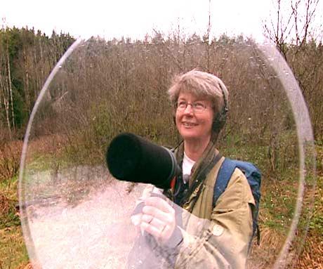 Helene Lampe forsker på lydene til fuglesnapperen. Her er hun i Sørkedalen og gjør lydopptak. Den store skjermen på parabolmikrofonen fanger opp lydene godt.