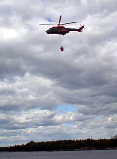 Et svensk og et norsk helikopter bombet skogen med vann i flere timer før flammene var under kontroll. Vannet ble hentet i Kornsjøene nær ved brannstedet. Foto Rainer Prang NRK.