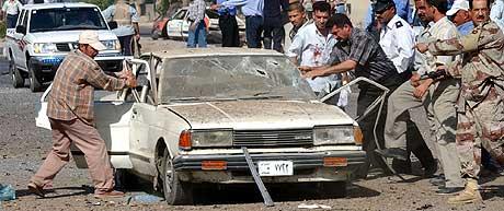 MINST 10 BILER BLE ØDELAGT: Her forsøker irakere å hente ut omkomne fra en av bilene som ble rammet av bilbomben i Bagdad. (Foto: AP/Hussein Malla)