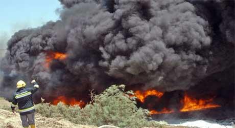 En irakisk brannmann i aksjon ved en oljebrann 27. juni i år. (Foto: Scanpix/Reuters)