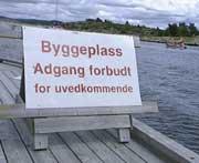 Et skilt forteller om at det ikke er lov å gå på byggeplassen. Likevel bodde det folk i hyttene, og turister gikk rundt og kikket da NRK var der tirsdag. ( Foto: Kathrine Brønn, BRK )