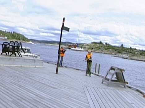 Barna står og fisker på brygga rett bak skiltet der det står adgang forbudt på byggeplassen. ( Foto: Kathrine Brønn, NRK )
