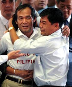 Angelo de la Cruz og hans bror Willie feller gledestårer etter Angelos ankomst til Manila i dag. (AFP/Scanpix)