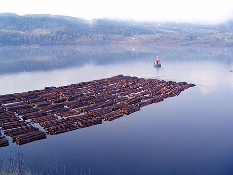 I Skiensvassdraget går en båt og sleper på store bunter med tømmer. Foto: Terje Sjøvaag