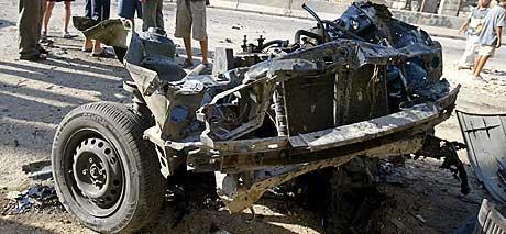 BILBOMBE: Ingen ble såret men bilen ble fullstendig ødelagt da en bilbombe eksploderte i nærheten av Sarafiya-bruen i Bagdad. (Foto: Saeed Khan/AFP)