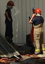 Brannmannskaper og etterforskere på vei inn i tregårdene. (Foto: MidtNytt)