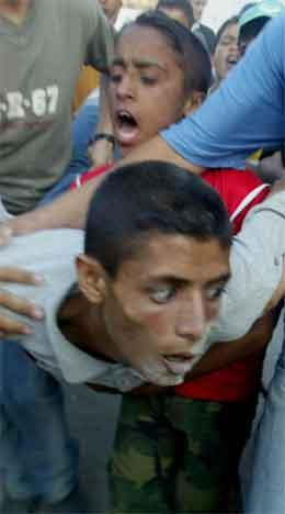 Ein skadd palestinsk ungdom blir hjulpen bort av kameratar. (Foto: AFP/Scanpix)