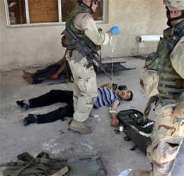 FØRSTEHJELP: Soldatene prøvde å lege skadene til fangene, før de fikk ordre om å trekke seg tilbake. (Foto: Ap Photo/The Oregonian)