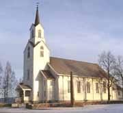 Bø kyrkje. Kyrkjelyden i Bø er i mot sal av prestegarden i Bø.