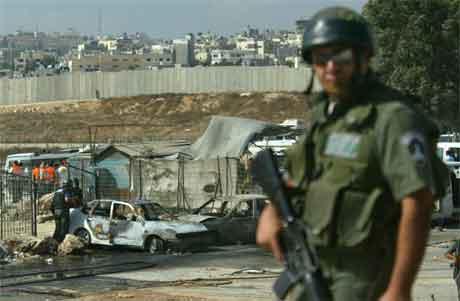 Ein israelsk soldat held vakt medan andre går sjekkar bilane som vart skadde i eksplosjonen. (Foto: AFP/Scanpix)