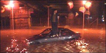 Denne bilen begynte plutselig å flyte rundt av seg selv da føreren forsøkte å krysse Holmen. Det eneste tørre stedet for mannen var på taket av bilen. (Foto: Harald Inderhaug)