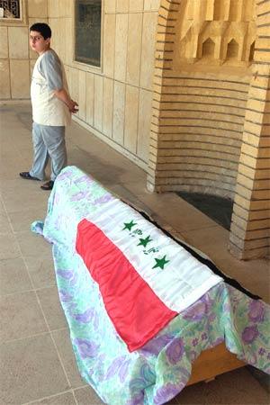 Omar Bashar står ved sin døde fars kiste. Han var politimann i Bagdad, men ble drept av en bilbombe. (Foto: AP/Scanpix)