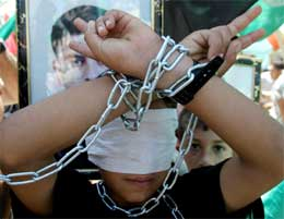 Palestinsk gutt i lenker gjør seierstegnet under en demonstrasjon til støtte for de sultestreikende (Scanpix/AP)