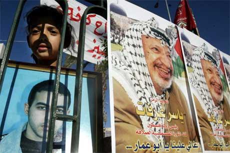 Ei palestinsk jente holder opp et bilde av sin fengslede bror under en demonstrasjon. Andre bærer bilde av Arafat (Scanpix/Reuters)