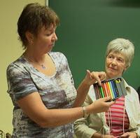 Lærer Marianne Kige forklarer om fargeblyantene elevene skal få - klasseassistentene følger med.