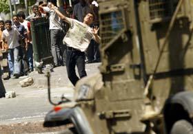 Palestinske ungdommer kastet stein mot en israelsk jeep som deltok i en militæroperasjon på Vestbredden i dag. (Foto: J. Ashtiyeh, AFP)