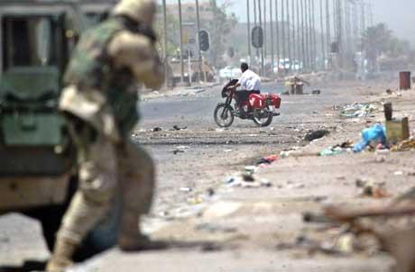 De amerikanske styrkene i Irak har åpnet en ny front mot den sjiamuslimske Mehdi-militsen ved å rykke inn i Sadr-byen i Bagdad, Her en amerikansk soldat i en av gatene i bydelen.  (Foto: David P. Gilkey / Pool / Reuters / Scanpix)