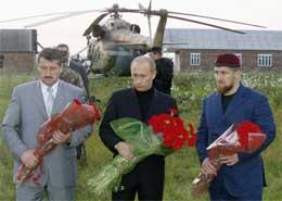 Putin og Alu Alkhanov (t.v.) ved Kadyrovs grav. Til høyre Kadyrovs sønn Ramzan (Scanpix/AP)