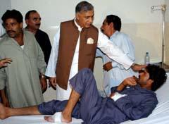 Daværende finansminister Aziz besøker en av de sårede etter bombeangrepet der han selv var mål. (Foto: AP)