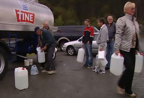 Folk lette fram bøtter og spann og kom strømmende til melkebilen, som denne gang kom med kildevann. Foto: Bernt Baltzersen.
