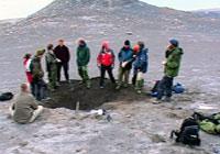 Profesjonelle og amatører samlet rundt utgravingsgropen på Svalbard. Foto: NRK