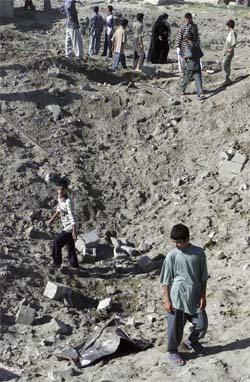 En irakisk gutt i krateret etter det amerikanske bombeangrepet i Falluja i dag. (Foto: Reuters/Scanpix)