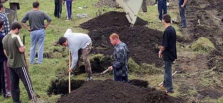 BEGRAVER SINE DØDE: Innbyggere i Beslan må klargjøre mange graver etter gisseldramaet. Søndag ble drøyt 20 ofre stedt til hvile. (Foto: Musa Sadulayev/AP)