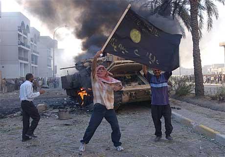 En tilhenger av Abu Musab al-Zarqawi vifter med et flagg ved et brennende amerikansk militærkjøretøy på Haifa-gaten 12. september. (Foto: Scanpix / AP / Hussein Malla)