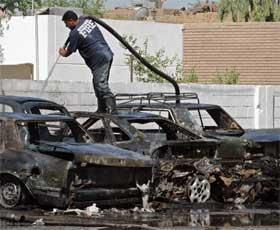 KRAFTIG BOMBE: Irakisk brannvesen slukker branner i flere biler som ble totalvrak i eksplosjonen. (Foto:REUTERS/Aladin Abdel Naby)