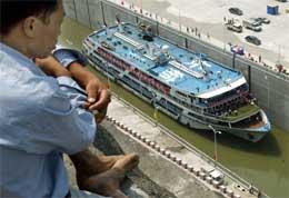 En arbeider på bredden ser ned på det første prøveskipet som går gjennom kanalen knyttet til anlegget (Scanpix/AFP)