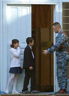 En politimann i Nord-Ossetia lar barna få se sin nye skole, noen dager før skolestart.(Foto:Scanpix)