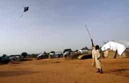 En sudansk gutt setter opp en drage i en av de mange leirene for folk som er jaget fra hjemmene sine i Darfur. (Foto: C.Bouroncle, AFP)