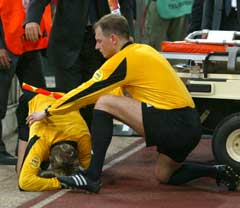 Andres Frisk får hjelp av en av linjedommerne etter å ha blitt truffet an en gjenstand. (Foto: AP/Scanpix)