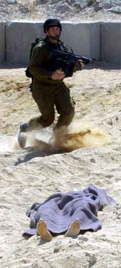 Ein israelsk soldat spring forbi liket av ein palestinar under kampane i busetjinga Morag på Gazastripa. (Foto: AFP/Scanpix)