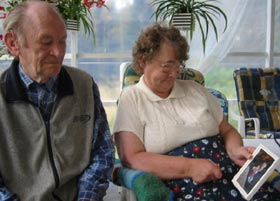 Marit og Adolf Bøgh ser på bilde av fosterdatteren. (Foto: Ann-Kristin Mo/NRK)