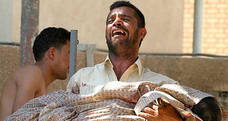 FORTVILTE FORELDRE: Mange av de drepte er barn. Her bærer en far bort sin døde sønn. (Foto: Ceerwan Aziz/Reuters)