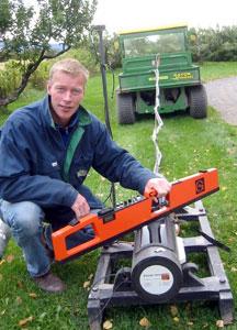 """Forsker Audun Korsæth ved Planteforsk Apelsvoll forskingssenter, Kapp med et instrument på en """"slede"""" og et sekshjula kjøretøy foran. (Foto: Vera Wold/NRK)"""