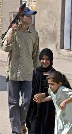 En opprørssoldat sammen med to barn i Sadr-byen i Bagdad. (Foto: AFP/Scanpix)