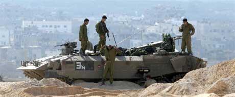 Israelske soldater vokter husene til israelske bosettere på Gazastripen. Flyktningleiren Jabalaya i bakgrunnen.(Arkivfoto: Scanpix)