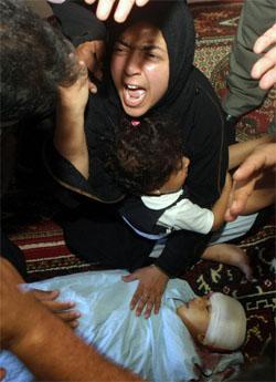 Moren til den fire år gamle palestinske gutten Louai al-Najar sørger over sitt barn, en av mange dødsofre i den israelske aksjonen på Gazastripen. (Foto: AFP/Scanpix)